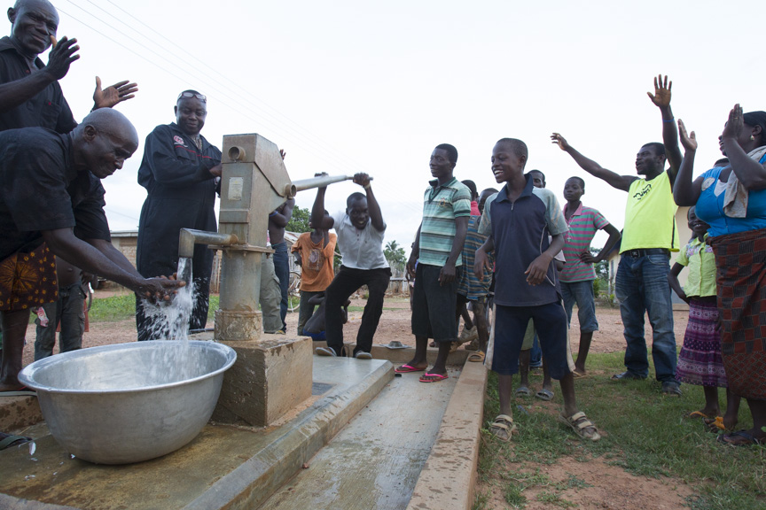 Residents cheer as water pours from a repaired water well in the village of Ampenkro, Ghana.