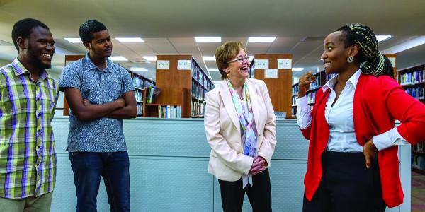 University President Margee Ensign, center, chats with students.
