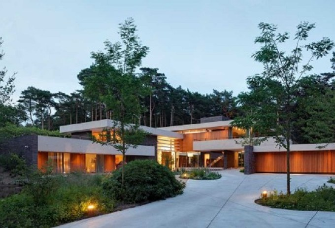 Home exterior with large swaths of natural wood which softly lit at night