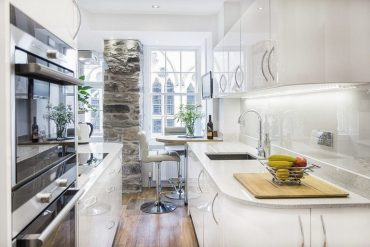Stone-wall-section-adds-character-to-the-tiny-kitchen-in-white-768x512