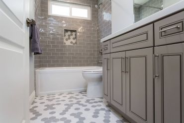 Transitional-style-bathroom-vanity-in-gray-along-with-white-and-gray-hexagonal-floor-tiles