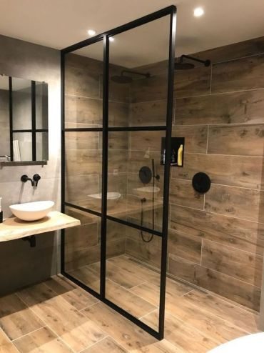 A-bold-contemporary-bathroom-with-wood-look-tiles-a-wooden-vanity-and-black-framing-for-a-dramatic-touch