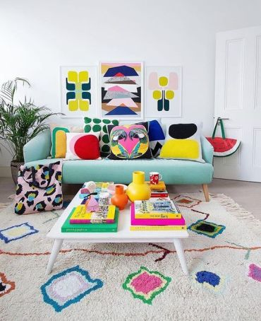 A-bold-summer-living-room-with-a-colorful-gallery-wall-bright-printed-pillows-and-a-rug-plus-bright-books-and-vases