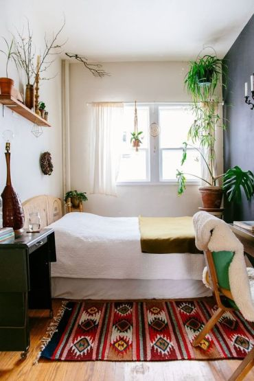 A-small-boho-bedroom-with-a-wooden-bed-desk-and-chair-boho-textiles-potted-plants-and-some-wicker-touches