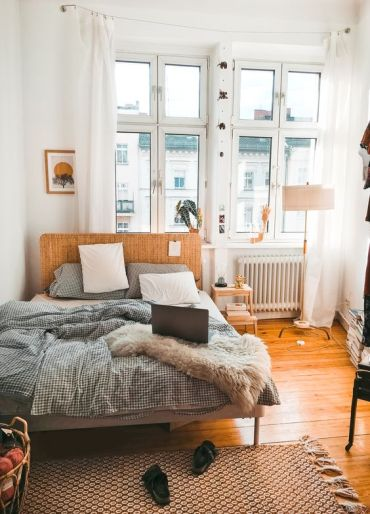 A-small-modern-bedroom-with-a-wicker-bed-a-floor-lamp-catchy-printed-textiles-and-a-rug-plus-white-curtains