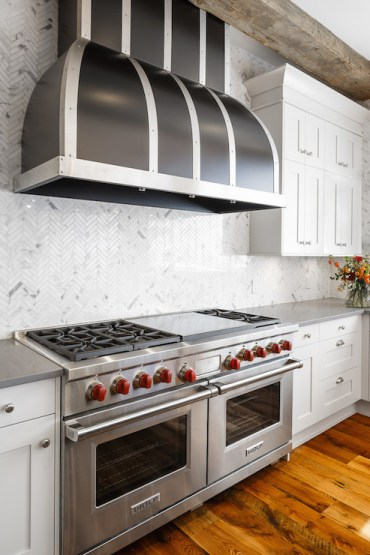 Black-dome-kitchen-hood-wolf-range-two-ovens-marble-herringbone-backsplash