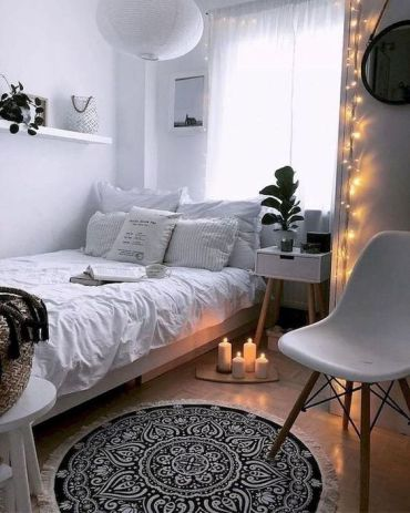 A-small-scandinavian-bedroom-with-white-walls-and-furniture-lights-candles-and-pendant-lamps