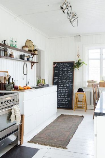 A-welcoing-and-light-filled-nordic-kitchen-with-shiplap-walls-a-white-floor-a-chalkboard-and-sleek-cabinets-plus-lights