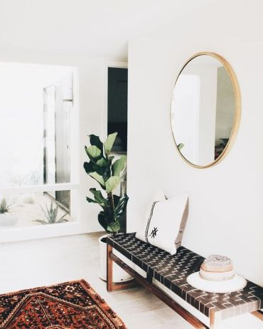 A-modern-entryway-with-a-leather-woven-bench-a-boho-rug-and-a-round-mirror-plus-a-statement-plant