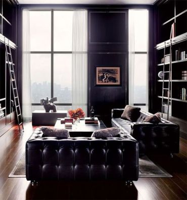 A-refined-living-room-with-black-leather-furniture-large-book-shelf-units-neutral-curtains-and-some-coffee-tables