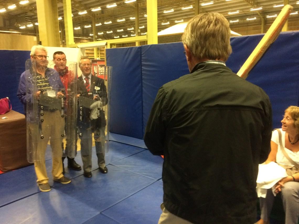 Rotarians Derek Davidson and Mike Fox warding off cricket bat wielding Paul Nickson