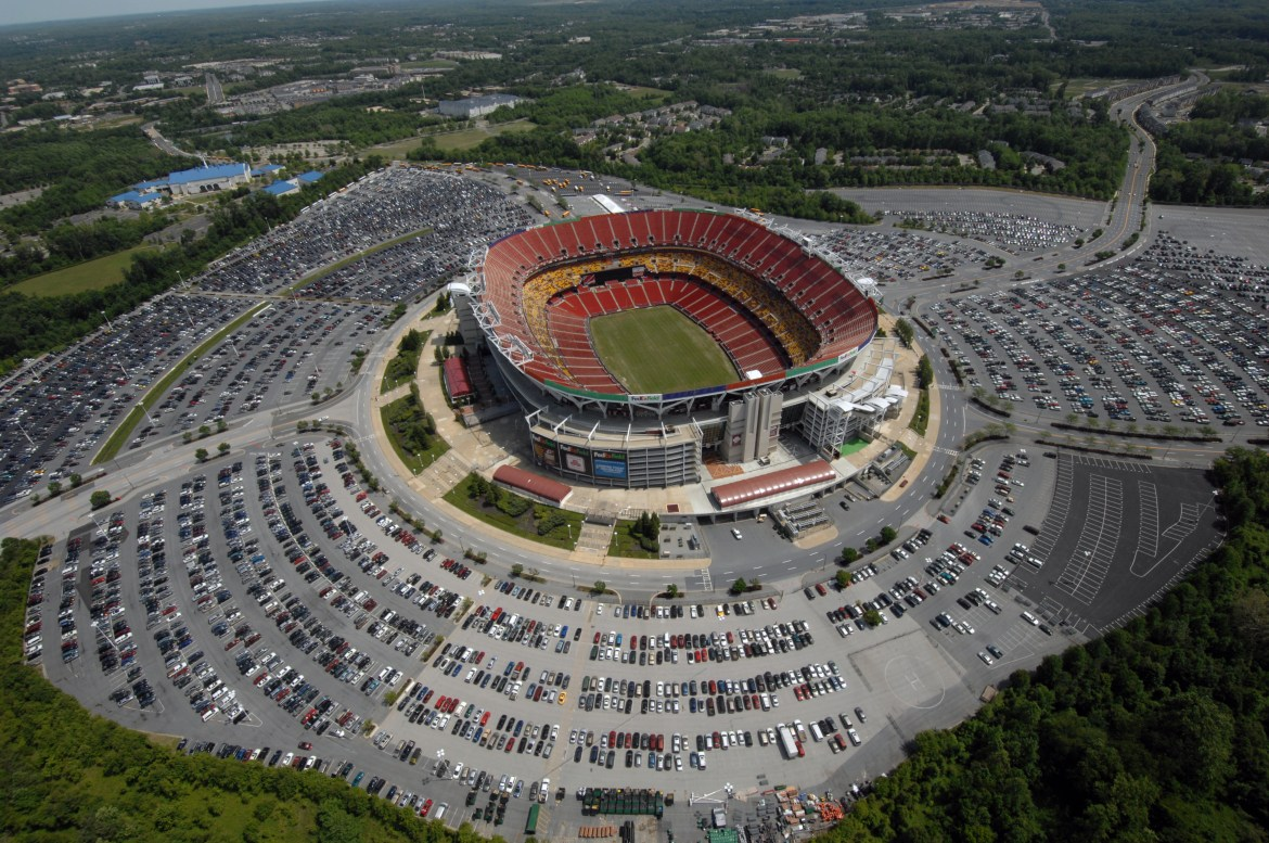 A large stadium, featuring burgundy and gold seating sections, is surrounded by a massive sea of parking. The lot is nearly filled.