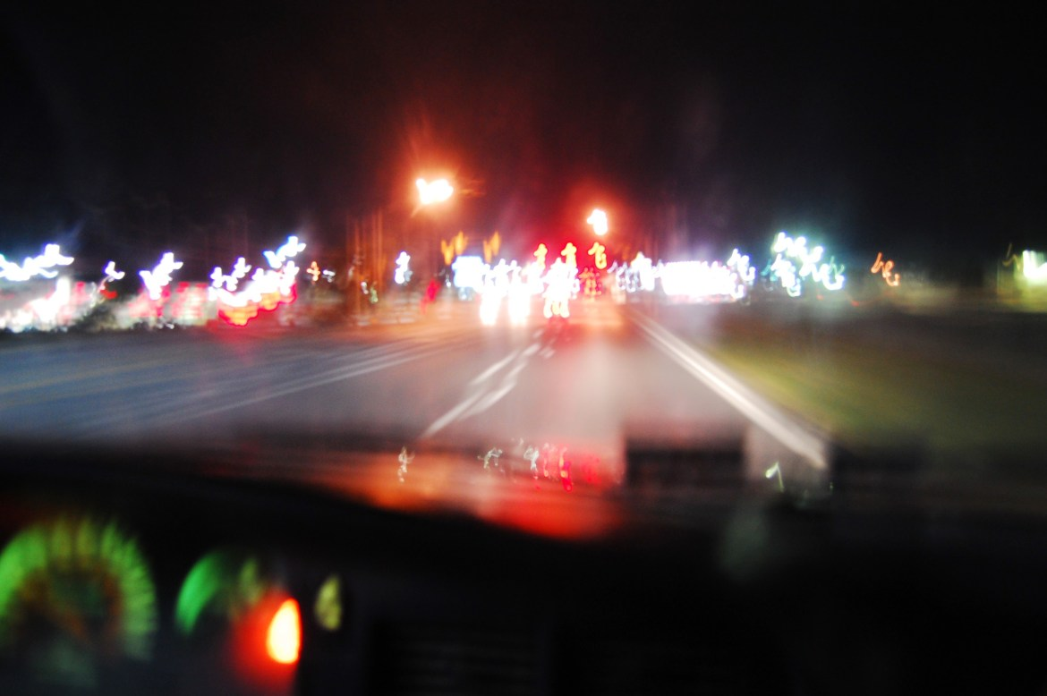 A blurry long exposure shows the forward-facing view of a car in motion shows a non-descript, four-lane roadway at night. The details are fuzzy and streaky. Ahead, a red light shines.