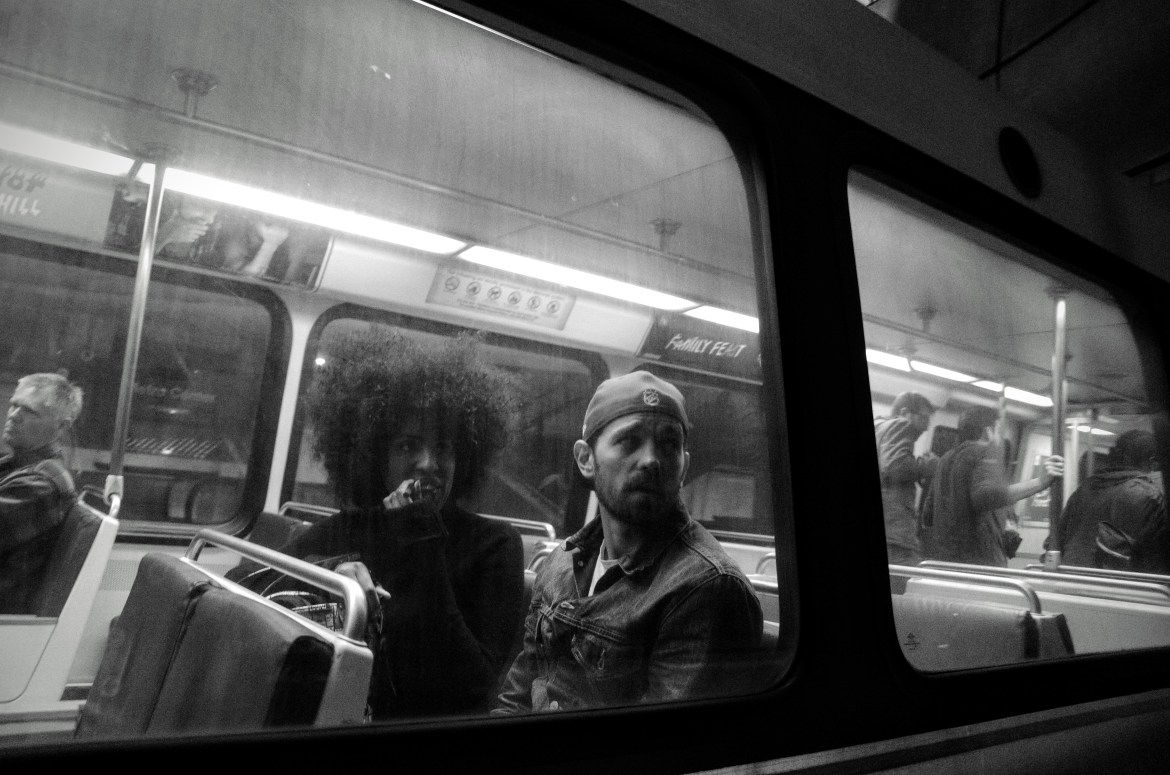 In a black and white photograph, a man and a woman sit inside a metrorail car. As seen from the outside of the car, the two are looking out of their window, the woman, with a large afro hairdo, applies lipstick. The man is wearing a backwards baseball cap and a denim jacket.