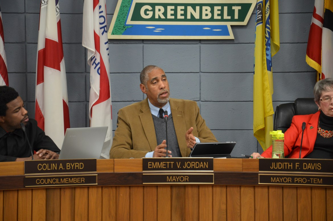 """A middle-aged African American man, wearing a brown jacket with a grey sweater and blue shirt, sits at a wood-paneled dais, gesturing as he speaks. Above and behind him, a sign reads """"Greenbelt."""" Infront of him, a placard reads """"Emmet V. Jordan, Mayor"""" To the left of him sits a younger African-American man wearing a dark shirt, infront of a placard reading """"Colin A. Byrd, Councilmember"""". To the right, an older white woman sits, wearing a matching red blazer and necklace, her nameplate reads """"Judith F. Davis, Mayor Pro-Tem."""""""