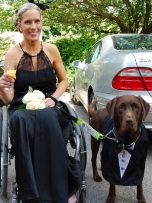 a photograph of a woman in a wheelchair holding the lead of an assistance dog