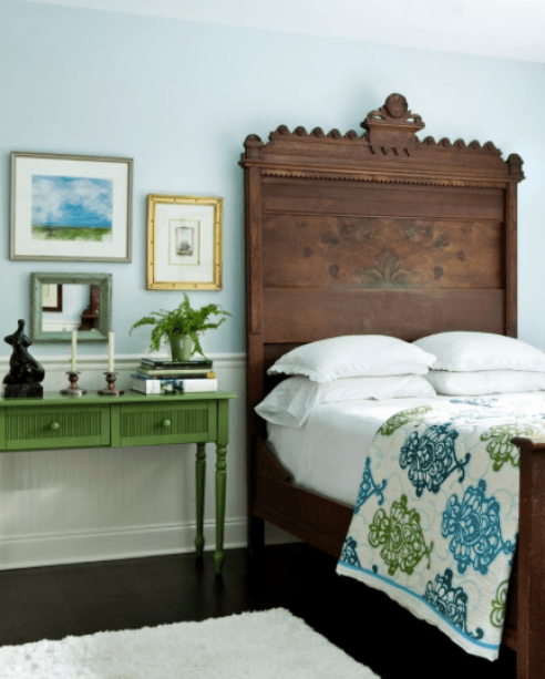 The soft blue wall colour keeps the room feeling open and breeze and contrasts with a rich green in fabrics and furniture.