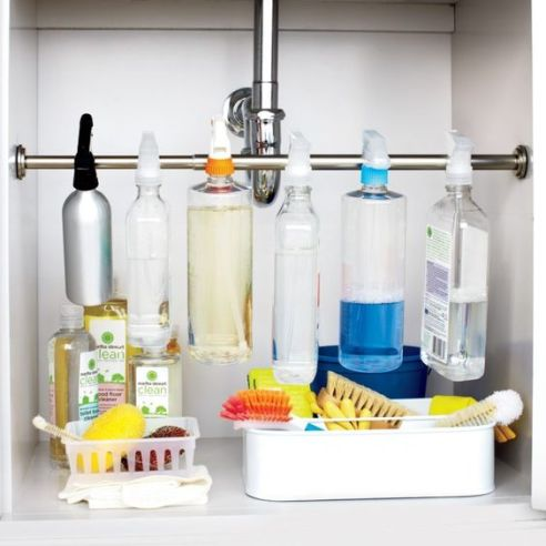 Organize the cabinet under the sink with a simple tension rod to hang bottles and create extra storage space.