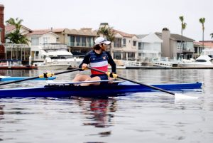 Galen Bernick in a single scull shell during practice. Looking over his shoulder in the harbor during practice.