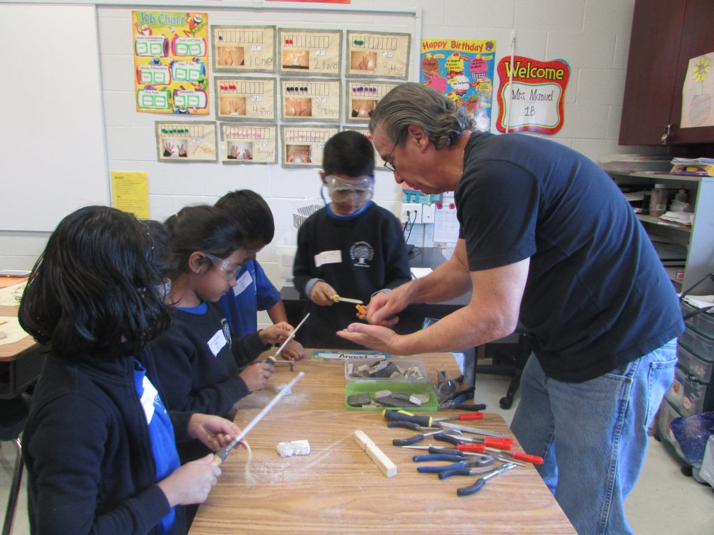 A parent demonstrating wood working skills in the classroom