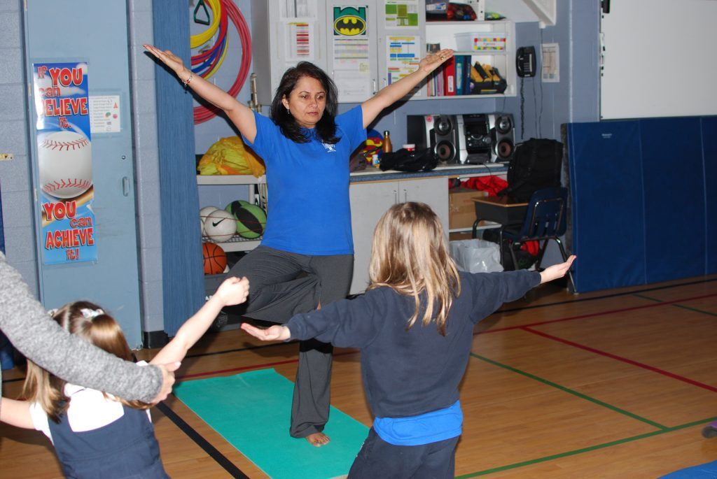 Teacher instructing the students in tree pose