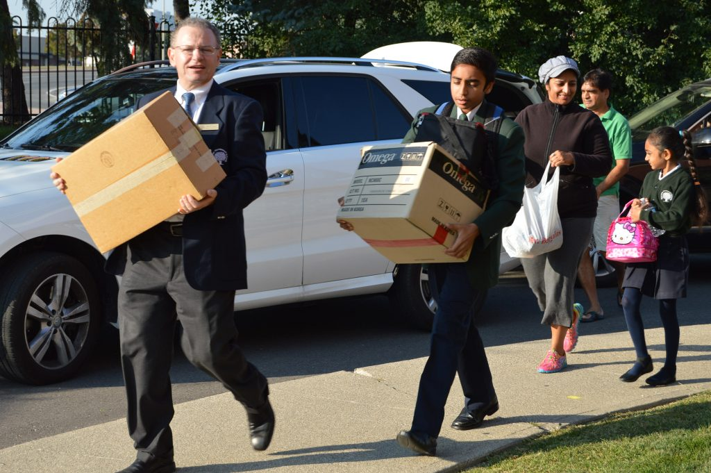 Faculty members, parents and older students at RMS helping the new students move in