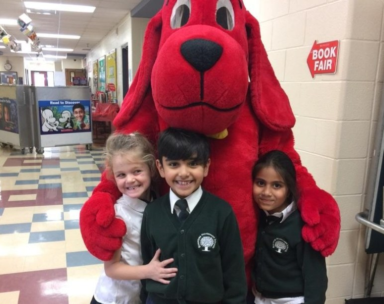 Three students hugging Clifford the Big Red Dog during the RMS Private School Book Fair in Brampton