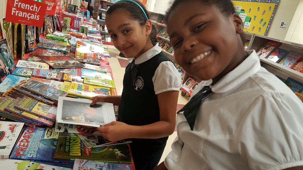 Two students at RMS Private School in Brampton looking at books during the book fair