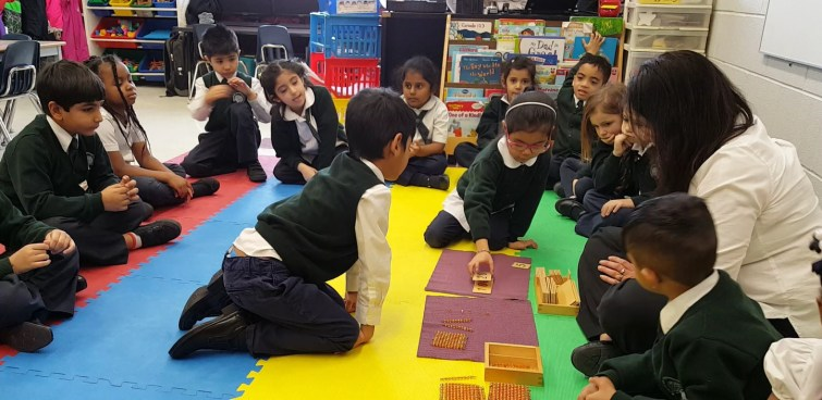 Kindergarten students using Montessori materials in private school to learn about math