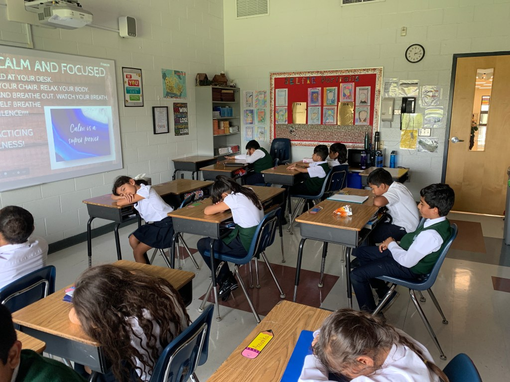 Students in a classroom practicing mindfulness