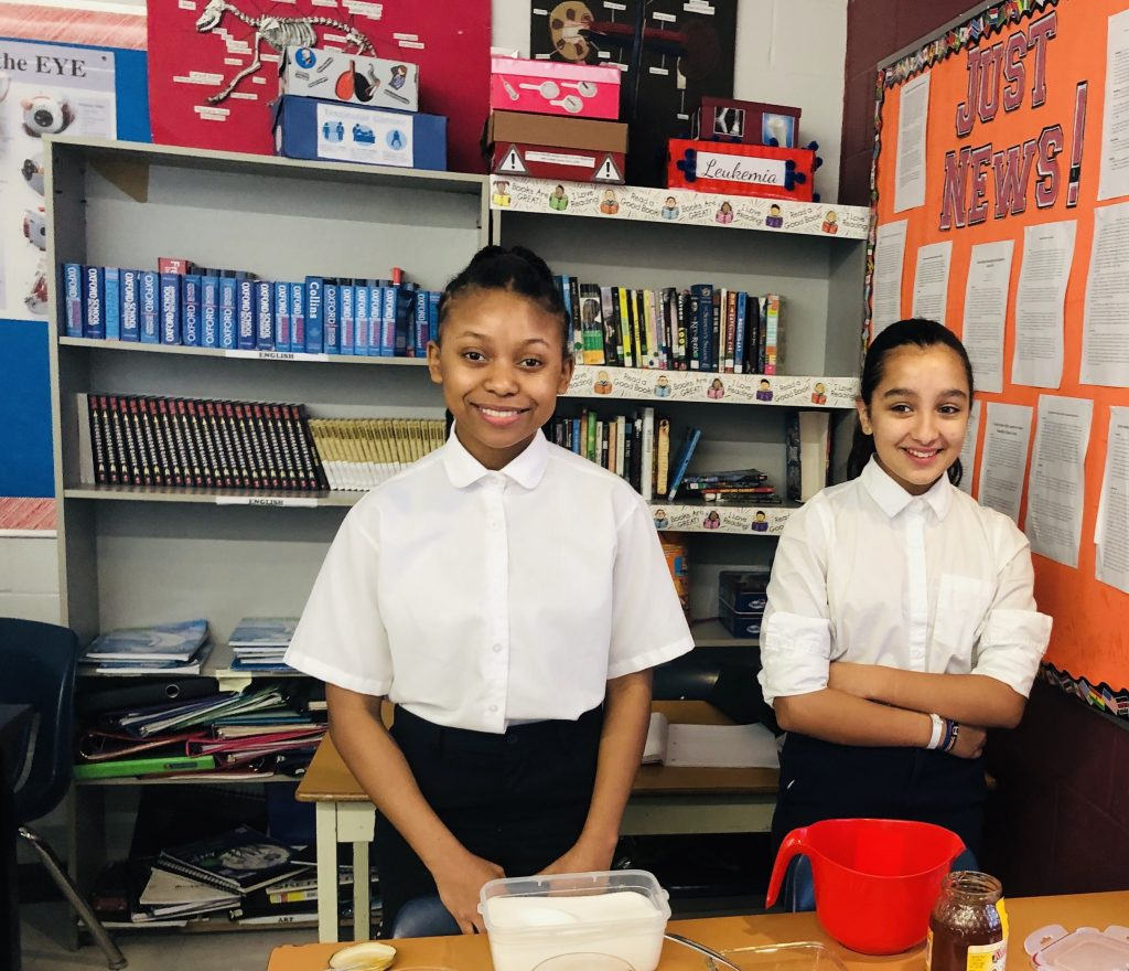 Two grade 8 students working on a science experiment using condiments