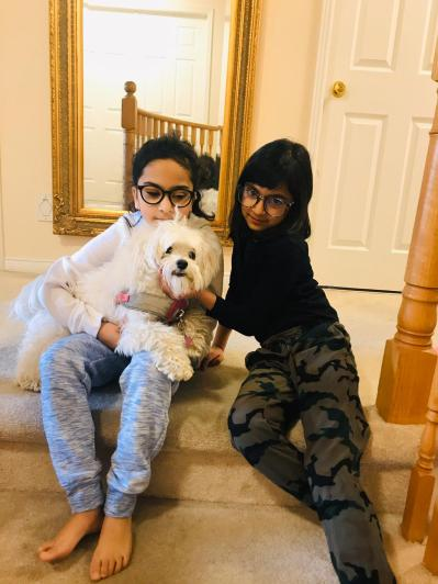Two sisters with a dog. There are numerous benefits to having a pet.