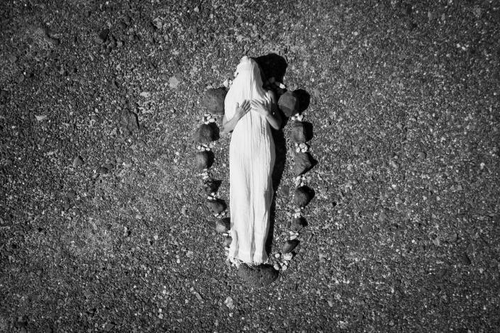 overhead photo of a woman on the rocks swaddled in a white cloth