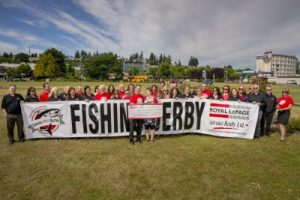 Surrounded by organizers and supporters, Stephen Grant, president of Royal LePage Advance, presents funds raised at the Royal LePage Advance Salmon Derby to Carrie Sjostrom of the Campbell River and North Island Transition Society. Photo:  Eiko Jones Photography.