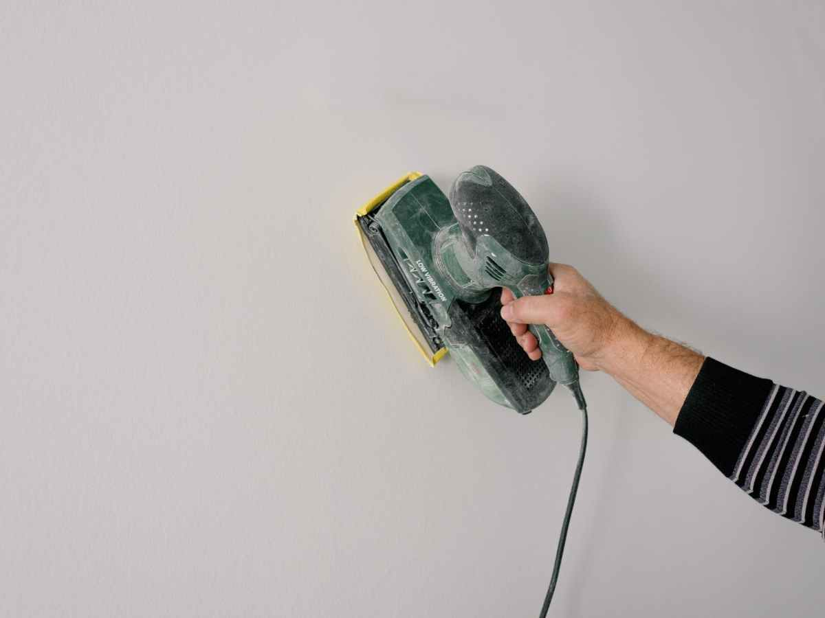 repairman polishing wall with construction tool