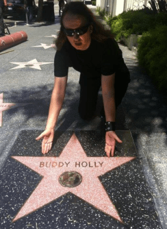 """On this day, September 7, 2011, Buddy Holly received his Hollywood Walk of Fame Star. I was there for the event and hung out with Buddy's wife María Elena and Phil Everly all day! My Mother, Barbara Orbison, always laughed when she saw this pic, She said """"It looks like you are giving him the star."""" I replied """"I did."""" It's another one of my behind the scenes contributions and it's a long story, but briefly, the year before I was with the board of the Walk of Fame and the Mayor of Hollywood at our Roy Orbison Star event and I begged and persuaded them that it was time for Buddy as well. There is quite a bit of work and """"politics"""" that goes into these star events and we got Buddy and Roy's stars on either side of the Beatles in front of the Capitol Records Building. Of course Buddy himself is responsible for his star, but I like to think I had a small part in this. My Mother was too ill to go so it was a sad day for me as well as a happy one. This was also the last time I saw my friend the great Phil Everly who I loved. Lots of stories too long to tell here"""