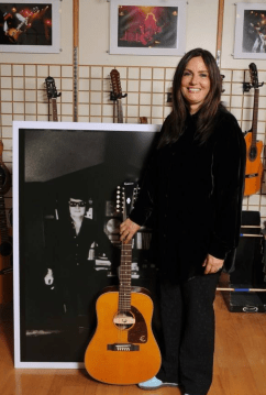 "Barbara Orbison at the Gibson Guitar offices in London,England with a limited edition ""Roy Orbison 12-string Epiphone called the ""Pretty Woman"" model."