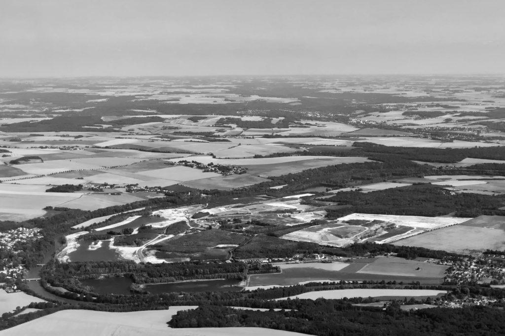 Photo noir et blanc. Des champs, des petites villes et villages, un fleuve vus du ciel.