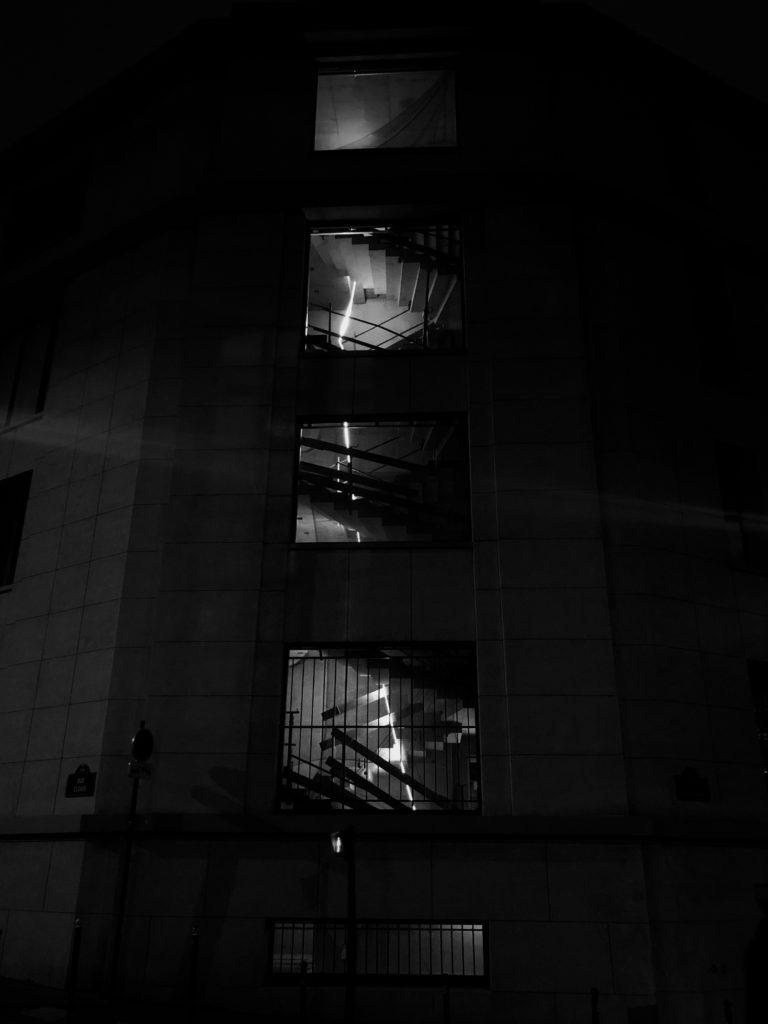 Photo noir et blanc. Une fibre lumineuse remonte un escalier en travaux vu depuis l'extérieur.