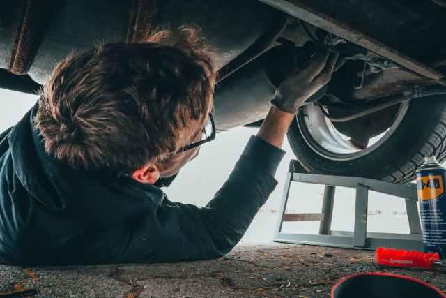 man fixing vehicle engine