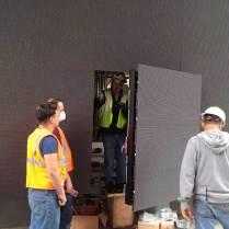 Workers installing Barco door display