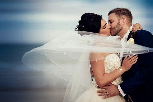Bride and groom portrait on Bournemouth beach with the veil flying