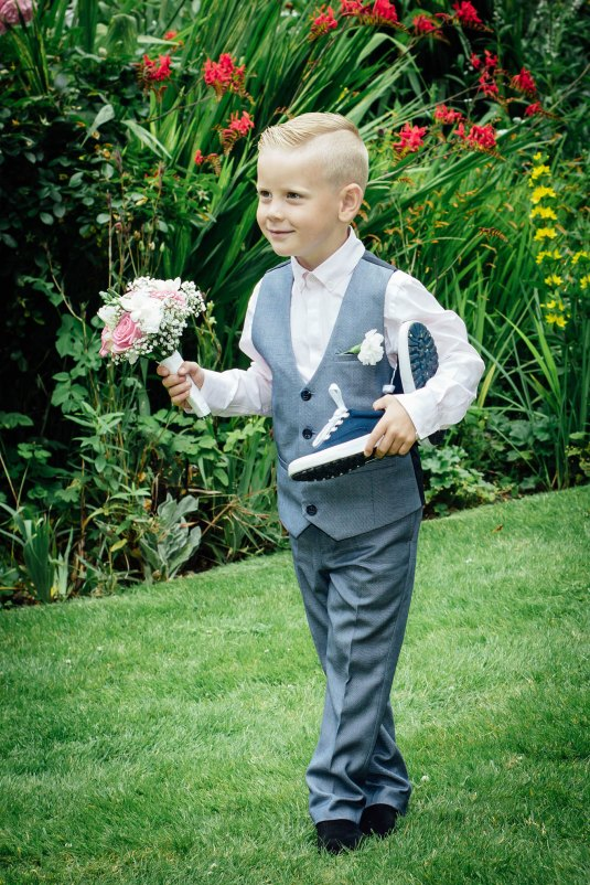 Page boy holding a bouquet of flowers