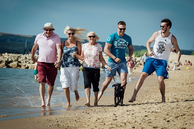 Family portrait photography Bournemouth - family running down the beach