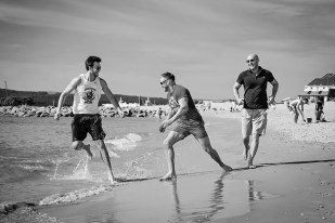 Portrait of family members running along the beach