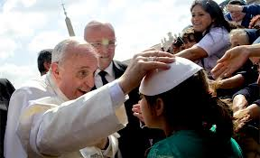 Pope Francis places his skull cap on a young girl's head