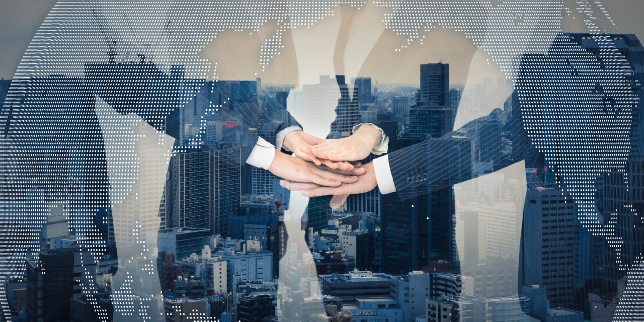 A business team gathers and puts their hands in together