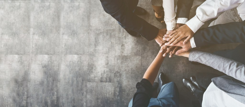 People in business attire stack their hands together in a sign of teamwork