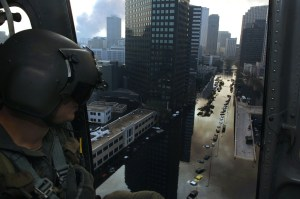 Helicopter rescue man looks out at flooded city streets