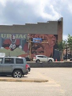 Artist Wes Hardin works on his mural of University of Alabama and NFL football star Wilbur Jackson in one of the most visible spots in Ozark, Jackson's hometown. (Julie Davis / Alabama NewsCenter)